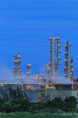 Refinery factory with green field on twilight