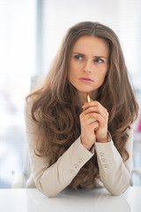Thoughtful business woman in office looking on copy space