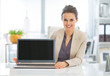 Happy business woman showing laptop blank screen