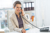 Fototapety Smiling business woman talking phone in office