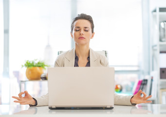 Business woman meditating near laptop