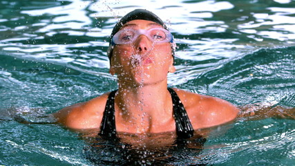 Funny female swimmer spouting water to camera in the swimming po