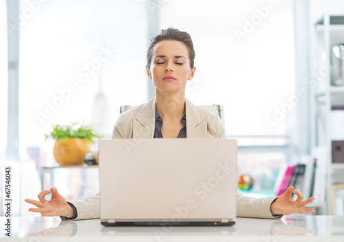 Business woman meditating near laptop