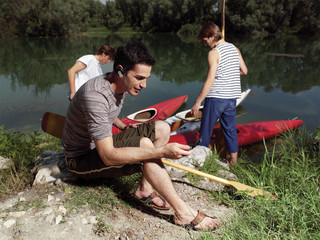 Young men with friends near river