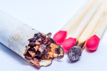 Closeup of smoked cigarette and matchsticks