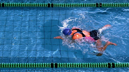 Fit female swimmer doing the breast stroke in swimming pool