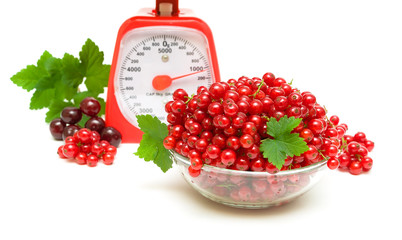 juicy redcurrants, kitchen scales and cherries on a white backgr