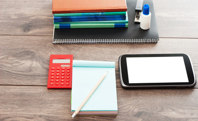stationery and electronic tablet on a wooden background