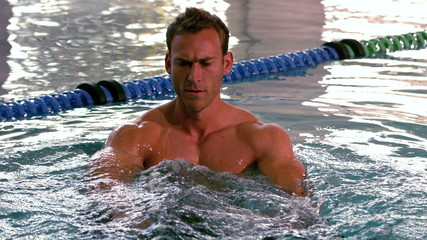 Muscular man working out with foam dumbbells in the pool