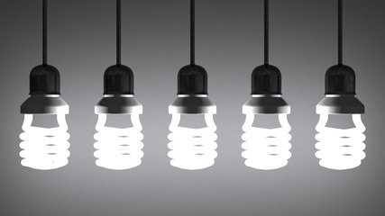 Hanging glowing spiral light bulbs on gray