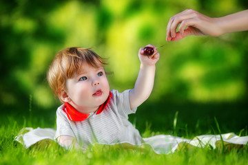 Happy baby have fun in the Park on a Sunny meadow with cherries.