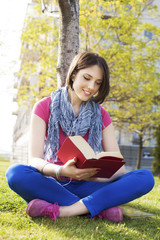 Beautiful happy young woman reading book in nature.