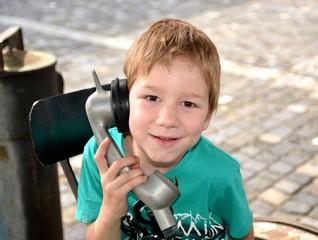Junge telefoniert mit altem Telefon