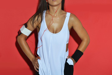 beautiful fitness woman posing against the red background