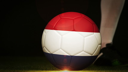 Football player kicking dutch flag ball