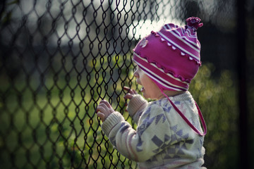 Little child behind a fence
