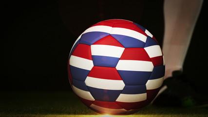 Football player kicking dutch flag ball