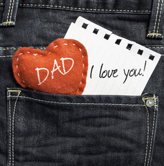 Dad I love you! written on a peace of paper on jeans background
