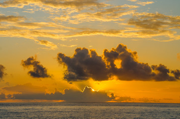 The sun rises behind clouds over the ocean.