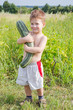 little boy with zucchini on field