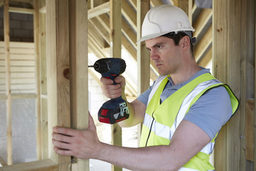 Construction Worker Using Cordless Drill On House Build