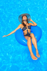 Young woman wearing a straw hat at the pool