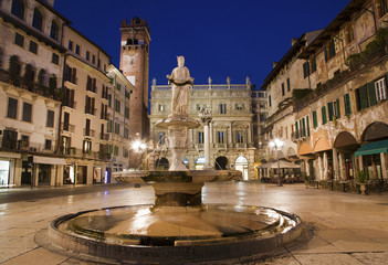 Verona - Fountain on Piazza Erbe in dusk and Porta Leona