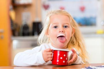 Mädchen trinkt Milch in der Küche