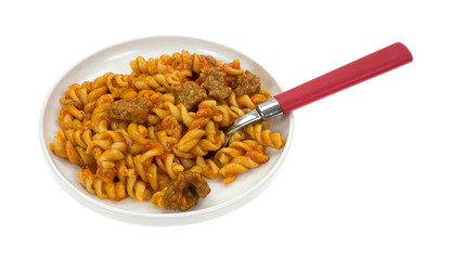 Cooked pasta and sausage on plate with fork