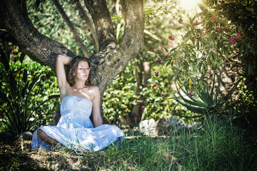 lady wearing elegant white dress relaxing in the forest