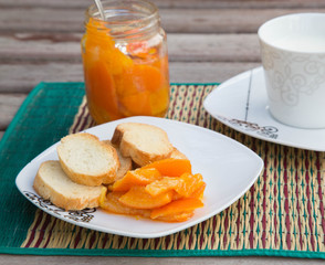 Homemade tangerine marmalade on the small square dessert plate