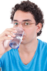 man in blue t-shirt with glasses looking at camera while drinkin