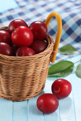Fresh plums in a wicker basket on a background of colored boards