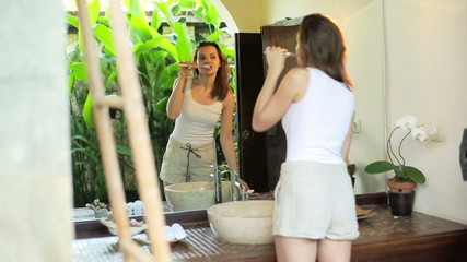 Woman brushing her teeth in front of the mirror in bathroom