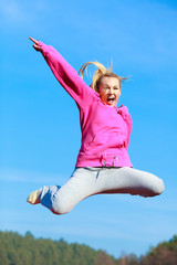 Cheerful woman teenage girl in tracksuit jumping showing outdoor