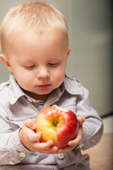 Little boy child kid eating apple fruit at home