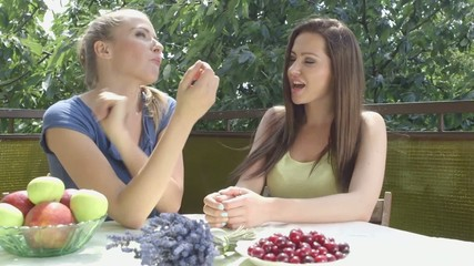 Two attractive smiling women having lunch time outside