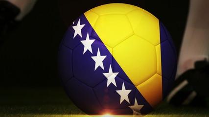 Football player kicking bosnia flag ball