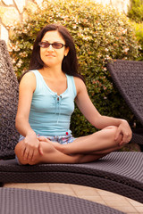 Woman Sitting On Sunbed In The Garden