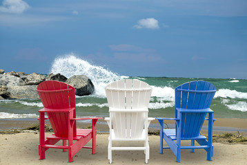 Adirondack chairs on beach with waves