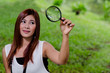 Pretty young woman holding a magnifying glass