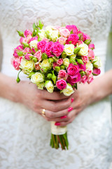 Closeup view of a bride holding bouquet of roses