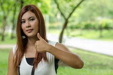 Attractive Asian woman giving a thumbs up
