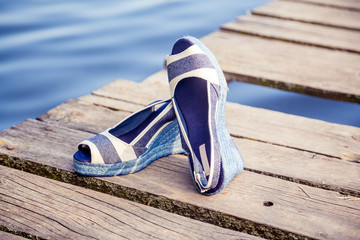 denim blue sandals lie on wooden clutch at the lake
