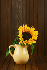 Still life with sunflower in vase on wooden background.