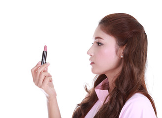 Beautiful woman applying pink lipstick