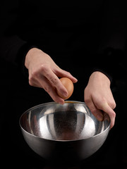 Hands breaking an egg