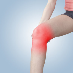 Acute pain in a knee. Female holding hand to spot of knee-aches.