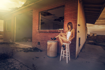 Beautiful young woman beside abandoned building