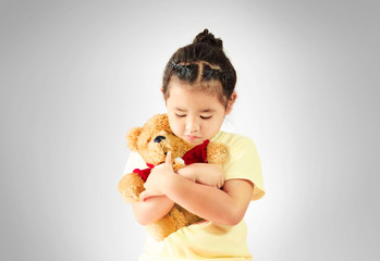 Sad little girl hugging teddy bear alone, studio shoot